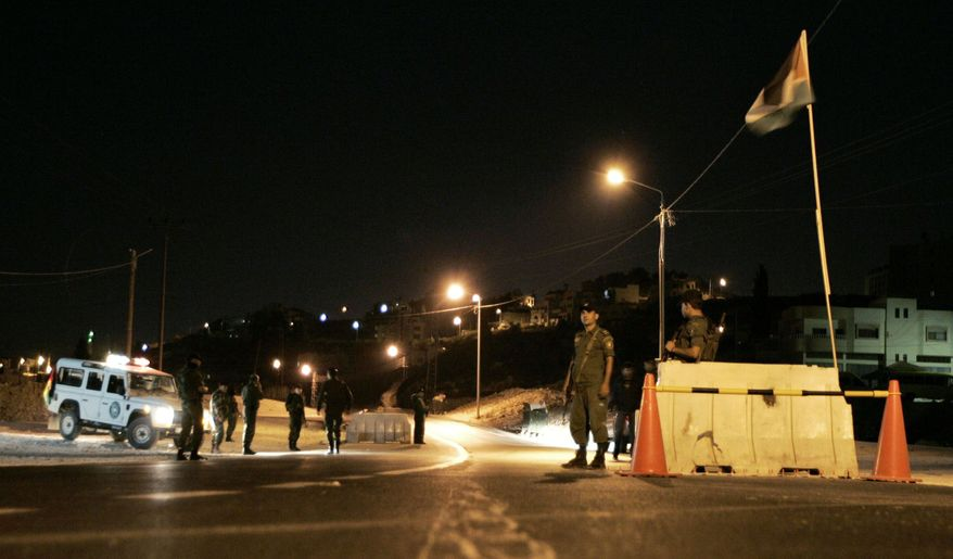 Palestinian security forces man a checkpoint in Nablus on the West Bank in late November. The U.S.-trained forces coordinate with Israeli troops, but some of them wonder if cooperation is sustainable and really helps their statehood goal. (Associated Press)