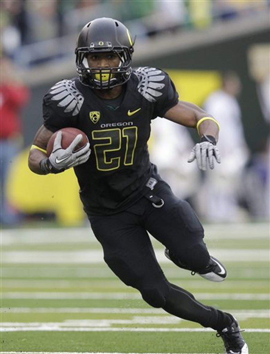 FILE - This Nov. 6, 2010, file photo shows Oregon running back LaMichael James carrying the ball during the third quarter of an NCAA college football game against Washington, in Eugene, Ore.  The small yet speedy sophomore is among the four finalists for the Heisman Trophy. (AP Photo/Rick Bowmer, File)