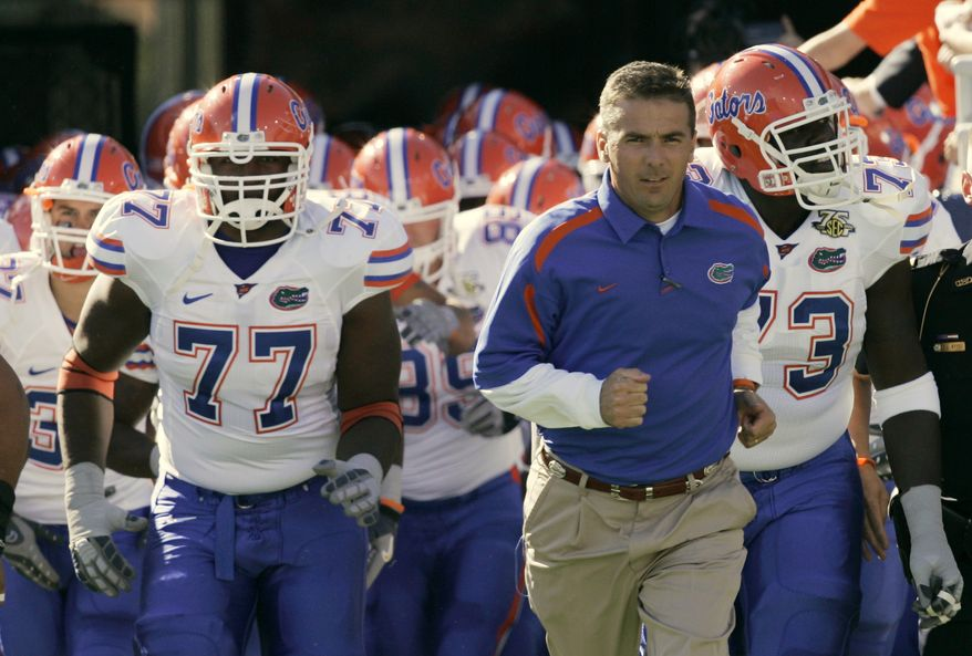 """FILE - In this Oct. 20, 2007, file photo, Florida coach Urban Meyer leads his team onto the field for their NCAA college football game against Kentucky in Lexington, Ky. Meyer is stepping down as coach after the Gators appearance in the Outback Bowl. In a statement released by the university on Wednesday, Dec. 8, 2010, Meyer says """"it is time to put my focus on my family and life away from the field."""" (AP Photo/Ed Reinke, File)"""