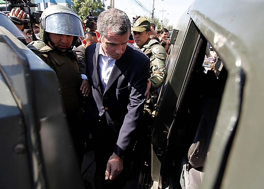 Chile's Justice Minister Felipe Bulnes enters an armored police vehicle as he leaves the San Miguel prison where a fire killed at least 81 prisoners in Santiago, Chile, Wednesday Dec. 8, 2010.  A prison fire set off during a riot killed at least 81 inmates at the Chilean prison on Wednesday and seriously injured at least 14 others, officials said. (AP Photo/Roberto Candia)