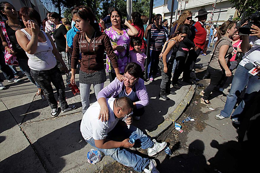 Relatives of inmates at San Miguel prison react as they wait for news after a fire killed at least 81 prisoners in Santiago, Chile, Wednesday Dec. 8, 2010.  The prison fire set off during a riot also seriously injured at least 14 others, officials said. (AP Photo/Aliosha Marquez)