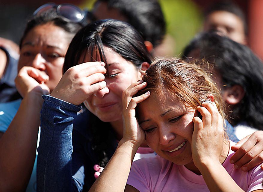 Relatives of inmates in San Miguel prison react as they wait for news after a fire killed at least 81 prisoners in Santiago, Chile, Wednesday Dec. 8, 2010. The prison fire set off during a riot also seriously injured at least 14 others, officials said. (AP Photo/Roberto Candia)