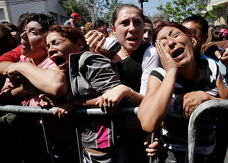 Relatives of prisoners at the San Miguel prison react as they listen the list of names of inmates who died in a fire in Santiago, Chile, Wednesday Dec. 8, 2010. The prison fire set off during a riot killed at least 81 and seriously injured at least 14 others, officials said. (AP Photo/Aliosha Marquez)