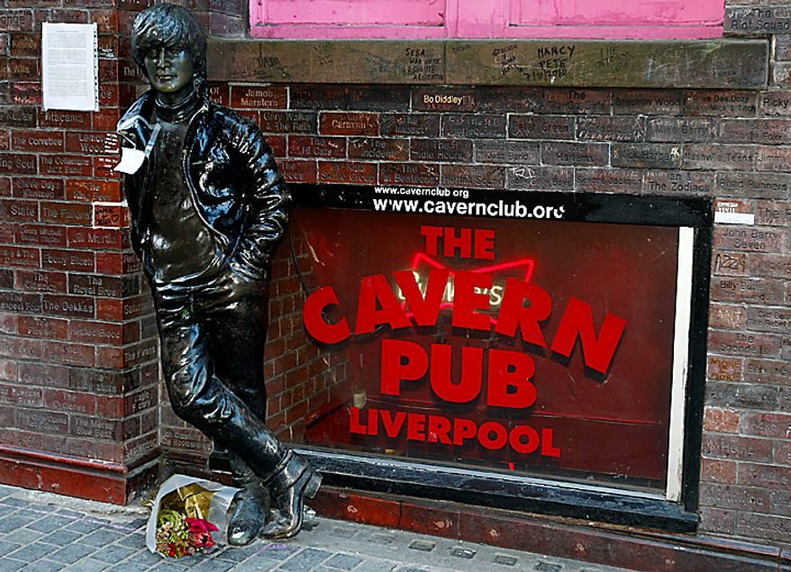 A note and flowers left at a statue of John Lennon outside the Cavern Pub in Mathew Street, Liverpool, England, Wednesday Dec. 8, 2010. Beatles fans planned to mark the 30th anniversary of John Lennon's death with a candlelit vigil at the city's European Peace Monument, which is dedicated to John Lennon. (AP Photo/Tim Hales)