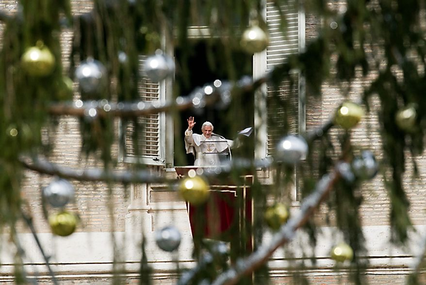 Pope Benedict XVI is framed through Christmas decorations as he delivers his blessing during the Angelus noon prayer from the window of his studio overlooking St. Peter's Square, at the Vatican, on the occasion of the Immaculate Conception of Mary, Wednesday, Dec. 8, 2010. (AP Photo/Andrew Medichini)