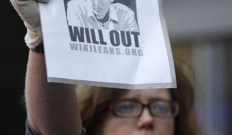 A supporter of whistle-blowing website WikiLeaks' founder Julian Assange holds up a placard outside the City of Westminster Magistrates Court in London where Mr. Assange was brought before a judge, Tuesday, Dec. 7, 2010. (AP Photo/Sang Tan)
