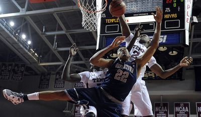 Georgetown's Julian Vaughn (22) pulls in a rebound over Temple's Michael Eric, left and Lavoy Allen in the first half of an NCAA college basketball game, Thursday, Dec. 9, 2010, in Philadelphia. (AP Photo/Michael Perez)