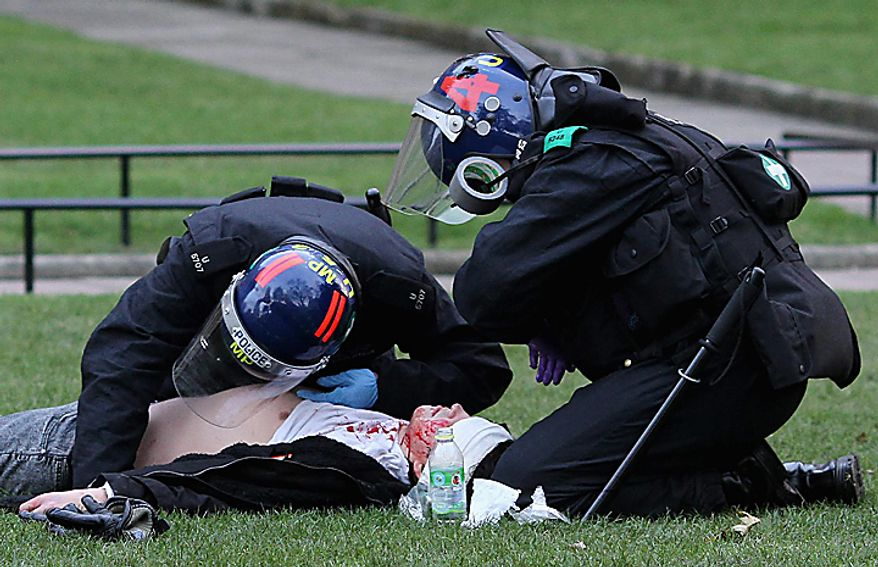 Police officers tend to an injured man outside the Houses of Parliament in London, Thursday Dec. 9, 2010, as police clashed with protesters marching to London's Parliament Square, while lawmakers debated a controversial plan to triple university tuition fees in England.(AP Photo/Gareth Fuller-pa)