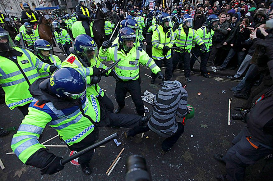 A police officer kicks a demonstrator during a protest against an increase in tuition fees on the edge of Parliament Square in London, Thursday, Dec. 9, 2010. Police clashed with protesters marching to London's Parliament Square as lawmakers debated a controversial plan to triple university tuition fees in England. (AP Photo/Matt Dunham)