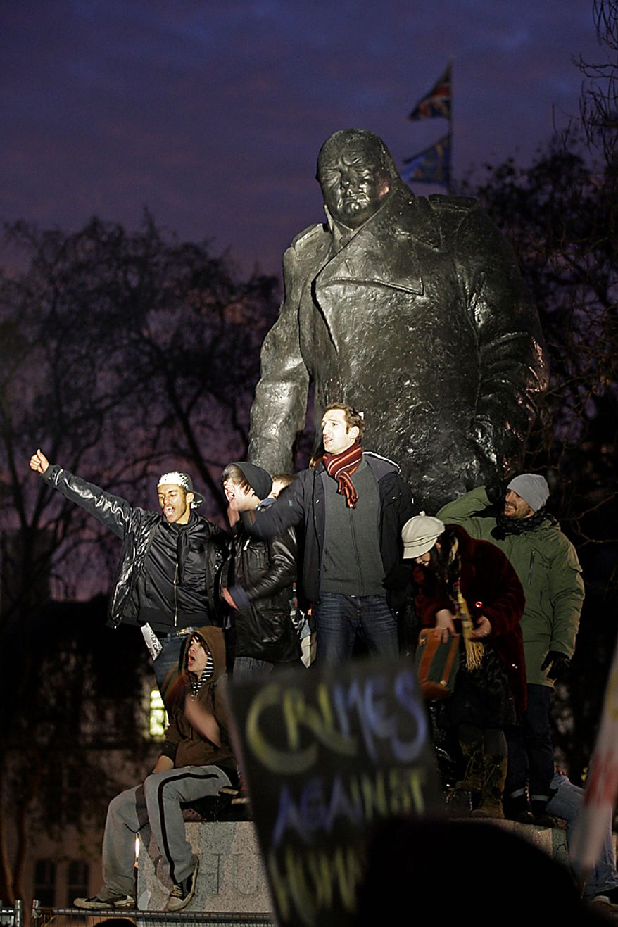 Protesters cry out as they stand on the statue of Winston Churchill at Parliament Square in London, as thousands of students demonstrate outside the Houses of Parliament in a protest against an increase in tuition fees, Thursday, Dec. 9, 2010. The House of Commons voted Thursday to increase tuition fees. (AP Photo/Sang Tan)