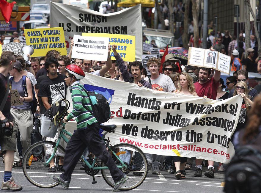 A cyclist rushes out of the way of hundreds of protesters marching through the city center to protest against the detention of WikiLeaks founder, Julian Assange, in Brisbane, Australia, Friday, Dec. 10, 2010. (AP Photo/Tertius Pickard)