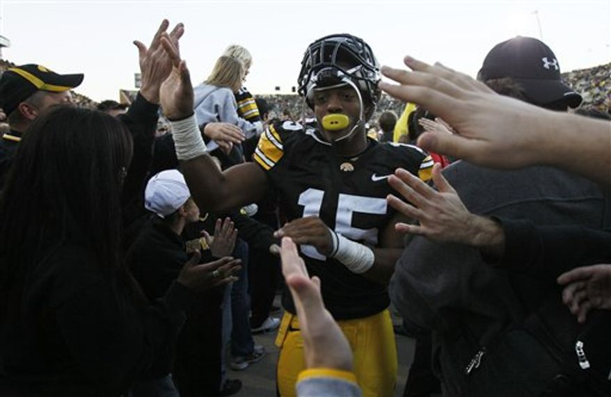 FILE - This Oct. 30, 2010, file photo shows Iowa wide receiver Derrell Johnson-Koulianos celebrating with fans after an NCAA college football game against Michigan State, in Iowa City, Iowa. Johnson-Koulianos has been released after making his initial court appearance on drug charges.  The 23-year-old and his roommate, 21-year-old Brady Cooper Johnson, were charged on Tuesday, Dec. 7, 2010, after police officers raided their Iowa City home. J (AP Photo/Charlie Neibergall, File)