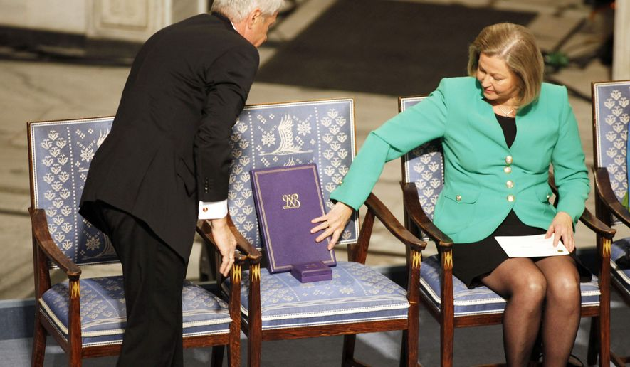 Nobel Commitee chairman Thorbjorn Jagland, left, and committee member Kaci Kullman Five place the Nobel Peace Prize medal and diploma on an empty chair representing Nobel Peace Prize laureate Liu Xiaobo during a ceremony honoring Liu at city hall in Oslo, Norway, on Friday Dec. 10, 2010. Liu, a democracy activist, is serving an 11-year prison sentence in China on subversion charges brought after he co-authored a bold call for sweeping changes to Beijing's one-party communist political system. (AP Photo/John McConnico)