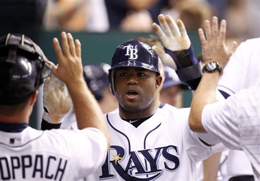 FILE - This July 27, 2010, file photo shows Tampa Bay Rays' Carl Crawford being congratulated after scoring in the sixth inning of the Rays' 3-2 victory over the Detroit Tigers in a baseball game in St. Petersburg, Fla.  Crawford has reached a preliminary agreement with the Boston Red Sox on a $142 million, seven-year contract, a person familiar with the negotiations told The Associated Press. The agreement is subject to Crawford passing a physical, the person said Wednesday night, Dec. 8, 2010.(AP Photo/Mike Carlson, File)