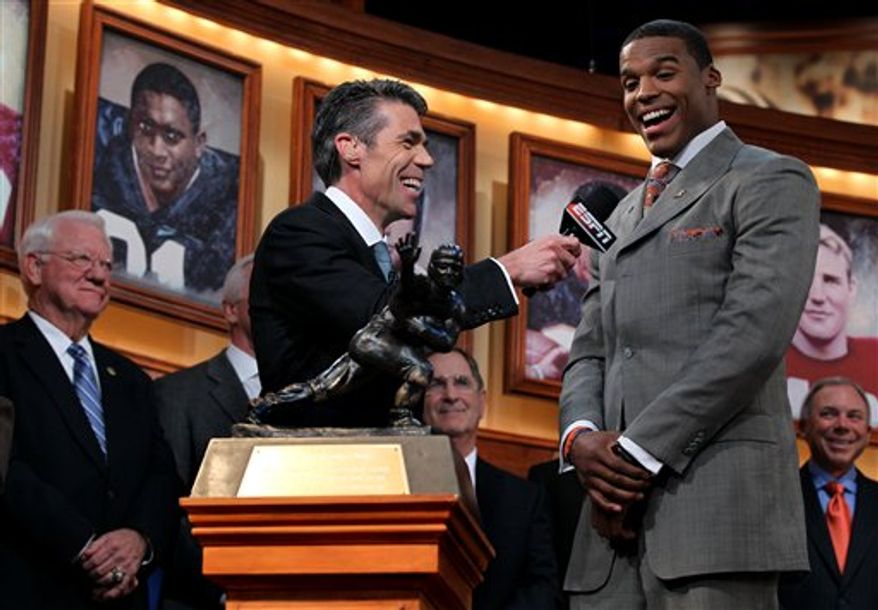 In this photo provided by the Heisman Trophy Trust, Auburn quarterback Cam Newton looks at the trophy while he makes his acceptance speech after being named the Heisman Trophy winner, Saturday, Dec. 11, 2010, in New York. (AP Photo/Heisman Trophy Trust, Kelly Kline)