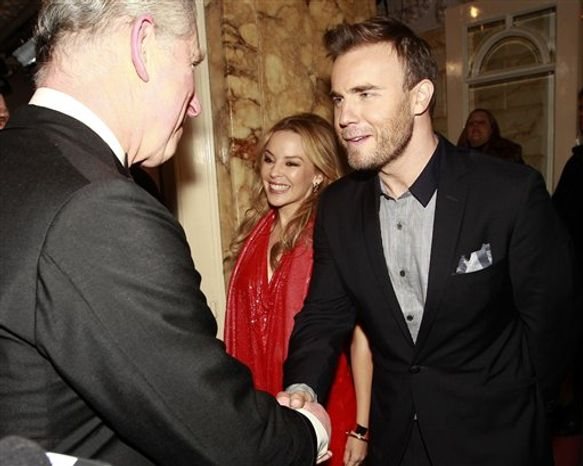 """Britain's Prince Charles shakes hands with Australian singer Kylie Minogue as he arrives to attend the Royal Variety Performance at the London Palladium, in London, Thursday Dec. 9, 2010. Shortly before, the car carrying the Prince and his wife the Duchess of Cornwall, had been attacked by rampaging students protesting against increased university fees. A group of up to 20 protesters, some chanting """"off with their heads!"""" smashed a rear window and splashed white paint on the vehicle. The couple were visibly shaken, but unharmed. Man at centre is unidentified.(AP Photo/Eddie Keogh-pa) UNITED KINGDOM OUT: NO SALES: NO ARCHIVE:"""