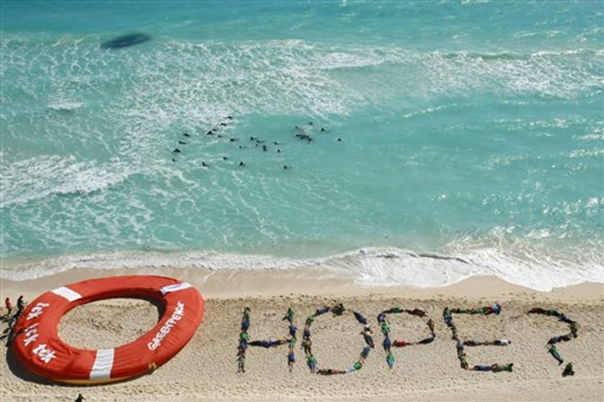 Greenpeace activists form the word hope as a question with their bodies, next to a giant life saver, during a demonstration near the site of the United Nations Climate Change Conference in Cancun, Mexico, Friday, Dec. 10, 2010.  (AP Photo/Israel Leal)