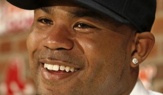 Carl Crawford smiles during a news conference announcing his signing a $142 million, seven-year contract for the Boston Red Sox at Fenway Park in Boston Saturday, Dec. 11, 2010. (AP Photo/Winslow Townson)