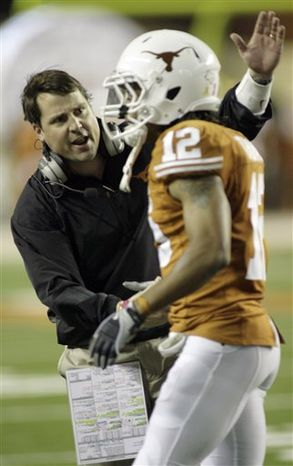 FILE-This Oct. 10, 2009 file photo shows Texas defensive coordinator Will Muschamp, left, congratulating safety Earl Thomas shortly after he grabbed a Colorado pass and returned it 92 yards for a touchdown during the third quarter of their NCAA college football game in Austin, Texas. A person familiar with the decision says Muschamp has accepted an offer to be the head coach at Florida. (AP Photo/Harry Cabluck,File)