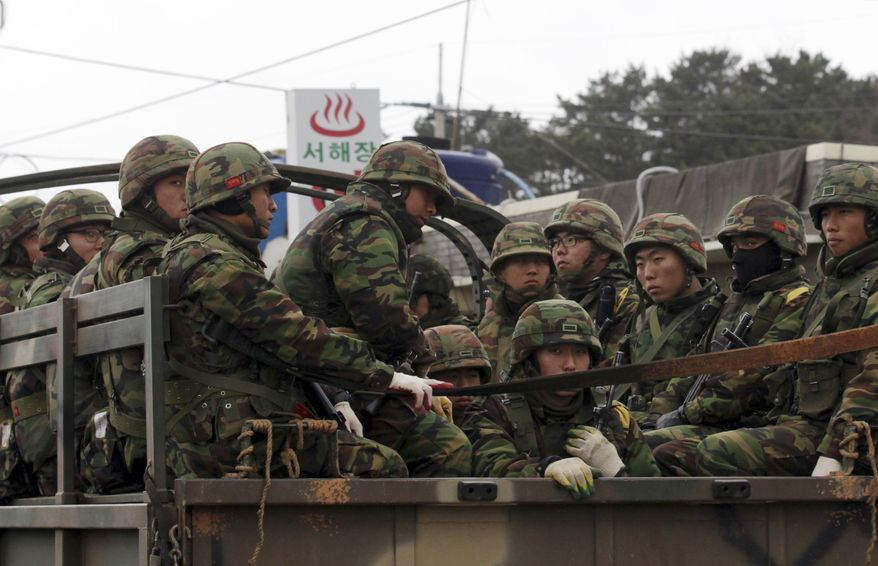 South Korean marines ride on the back of a truck on Yeonpyeong Island, South Korea, on Friday, Dec. 10, 2010. South Korean President Lee Myung-bak is pushing the idea of Korean unification, even as tensions remain high two weeks after the North shelled a South Korean island, killing four and setting the region on edge. (AP Photo/Yonhap, Kim Ju-sung)
