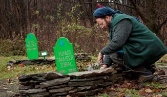 Hans Hass pauses Nov. 5 at a grave in the Sufi cemetery on the grounds of the Sufi center in Sidney Center, N.Y. The town was thrust into the spotlight this summer after a controversy over the Muslim grave sites. (Associated Press)