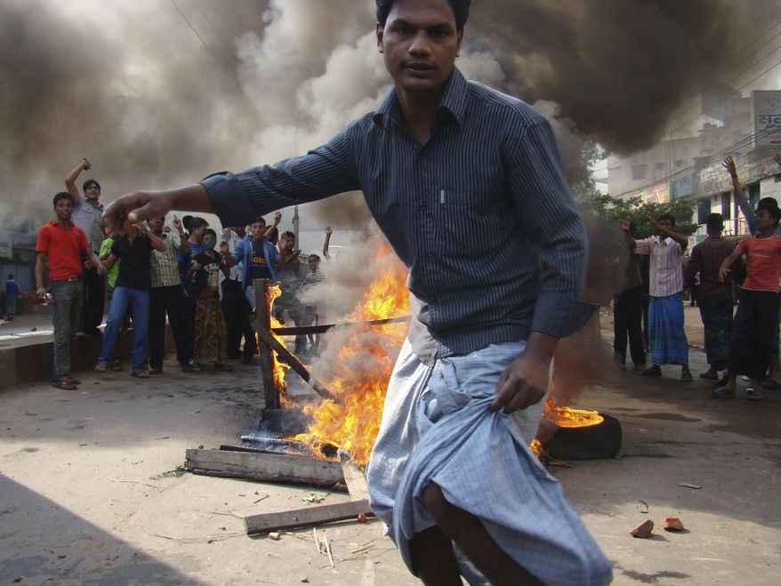 Protesting Bangladeshi garments workers burn tires and furniture to block traffic in Chittagong, Bangladesh, on Sunday, Dec. 12, 2010. Workers demanding the implementation of a new minimum wage clashed with police at an industrial zone, leaving up to three people dead and 100 hurt, police and news reports said. (AP Photo/Alauddin Hossain Dulall)