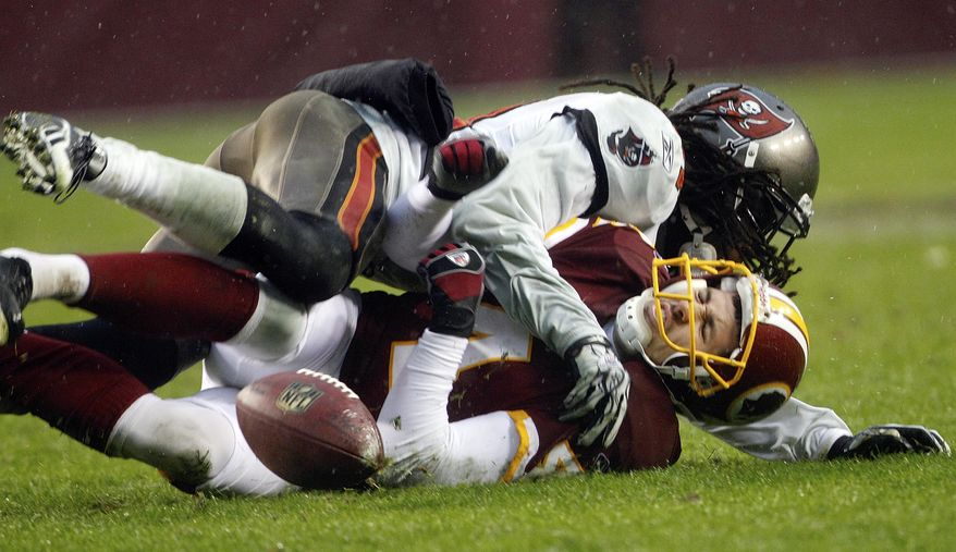 Washington Redskins placekicker Graham Gano (bottom) is tackled by Tampa Bay Buccaneers cornerback E.J. Biggers after Gano's extra point kick is botched during the second half of Tampa Bay's 17-16 victory Sunday in Landover, Md. (Associated Press)