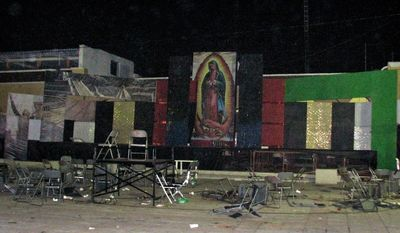 A large image of the Virgin of Guadalupe looms over the plaza where rival gangs held a gunbattle in Tecalitlan, in Mexico's Jalisco state, late Friday, Dec. 10, 2010. At least 11 people were killed, the Jalisco state attorney general's office said. (AP Photo/Raul Aguilar)