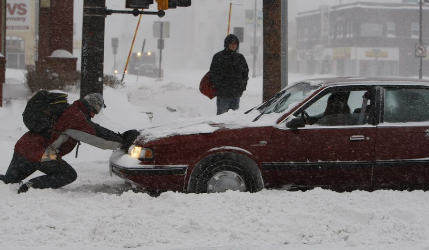 A good Samaritan tries to help free a woman's car from the snow as a winter storm hits St. Paul, Minn., on Saturday, Dec. 11, 2010. (AP Photo/Ann Heisenfelt)