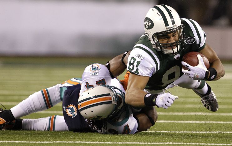 New York Jets tight end Dustin Keller (81) is tackled by Miami Dolphins cornerback Sean Smith (24) during the second quarter of the Dolphins' 10-6 road win on Sunday. (Associated Press)