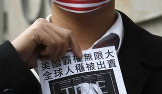 Supporters of WikiLeaks founder Julian Assange hold a banner,  wearing the masks featuring  the American National flags during a protest at Consulate General of the United States in Hong Kong Friday, Dec. 10, 2010. Skirmishes raged across cyberspace between WikiLeaks supporters and the companies they accuse of trying to stifle the group, with websites on both sides of the battle line taken out of service or choked off by attacks.  (AP Photo/Kin Cheung)