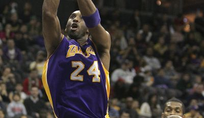 Los Angeles Lakers' Kobe Bryant (24) takes a jump shot as New Jersey Nets' Johan Petro (right) looks on in the second half during the Lakers' 99-92 win Sunday at the Prudential Center in Newark, N.J. (Associated Press)