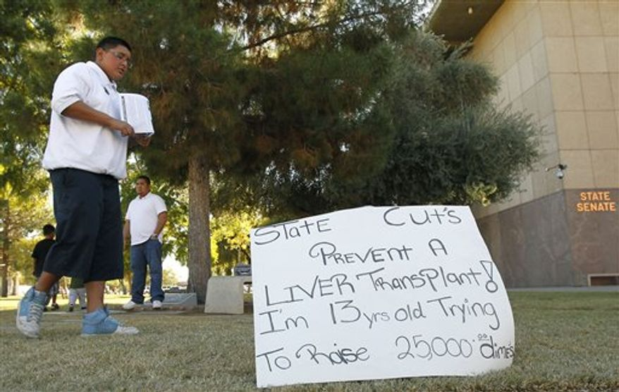 FILE - In this Dec. 7, 2010, file photo, 13-year-old Carlos Olivas paces in front of the Arizona Capitol in Phoenix to help raise money for his friend Francisco Felix who was denied a liver transplant because Medicaid suddenly won't pay for it. In Arizona, lawmakers stopped paying for some kinds of transplants, including livers for people with hepatitis C. When the cuts took effect Oct. 1, Medicaid patient Francisco Felix, 32, who needs a liver, suddenly had to raise money to get a transplant. (AP Photo/Ross D. Franklin, File)
