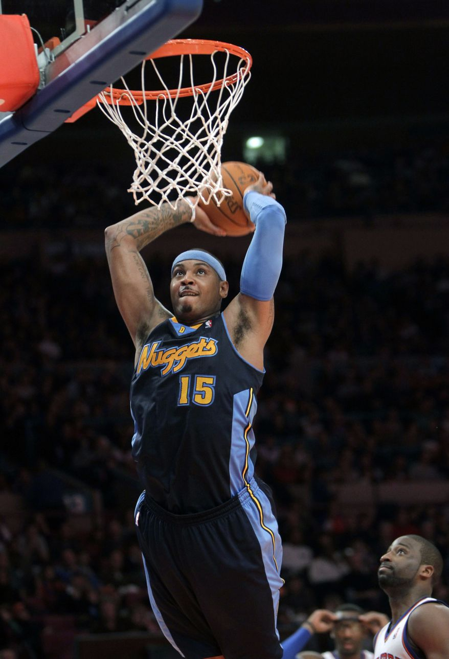 Denver Nuggets' Carmelo Anthony dunks the ball against the New York Knicks in New York on Sunday. The Knicks beat the Nuggets, 129-125. (Associated Press)