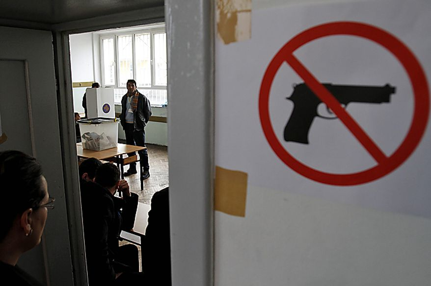 People vote at a polling station in general elections in Kosovo's capital Pristina on Sunday, Dec. 12, 2010. Kosovars vote in the first general poll since the country's declaration of independence from Serbia in 2008, a critical election already marred by ethnic tension that many fear will split the world's newest country.(AP Photo/Visar Kryeziu)