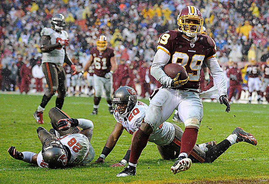 Washington Redskins wide receiver Santana Moss carries the ball across the goal line for a touchdown as Tampa Bay Buccaneers running back Kregg Lumpkin, left, and cornerback Ronde Barber lie on the ground during the second half of an NFL football game in Landover, Md., Sunday, Dec. 12, 2010. Tampa Bay defeated the Redskins 17-16. (AP Photo/Nick Wass)