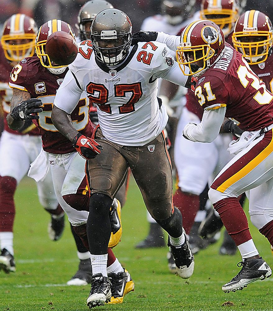 Washington Redskins cornerback Phillip Buchanon (31) strips the ball from Tampa Bay Buccaneers running back LeGarrette Blount (27) during the first half of an NFL football game in Landover, Md., Sunday, Dec. 12, 2010. The fumble was recovered by Washington Redskins cornerback DeAngelo Hall, left. (AP Photo/Nick Wass)