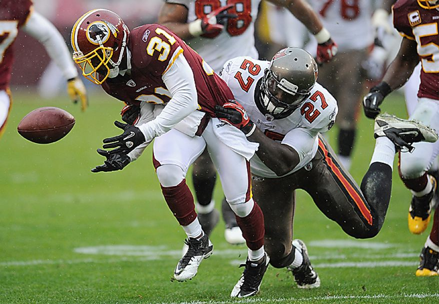 **FILE** Washington Redskins cornerback Phillip Buchanon tries to control the ball he stripped from Tampa Bay Buccaneers running back LeGarrette Blount during the first half of an NFL football game in Landover, Md., on Dec. 12, 2010. (Associated Press)