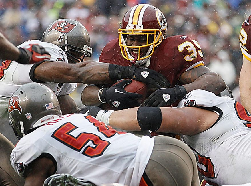 Washington Redskins running back Keiland Williams is stopped by a wall of Tampa Bay Buccaneers defenders including, linebacker Quincy Black, left, linebacker Geno Hayes, center, and defensive tackle Roy Miller, right, during the first half of an NFL football game in Landover, Md., Sunday, Dec. 12, 2010. (AP Photo/Evan Vucci)