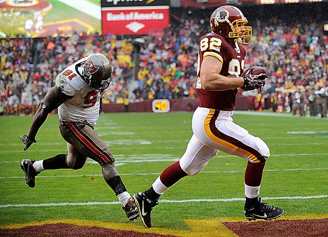 Washington Redskins tight end Logan Paulsen (82) carries the ball into the end zone for a touchdown as Tampa Bay Buccaneers defensive end Stylez White chases him during the first half of an NFL football game in Landover, Md., Sunday, Dec. 12, 2010. (AP Photo/Nick Wass)