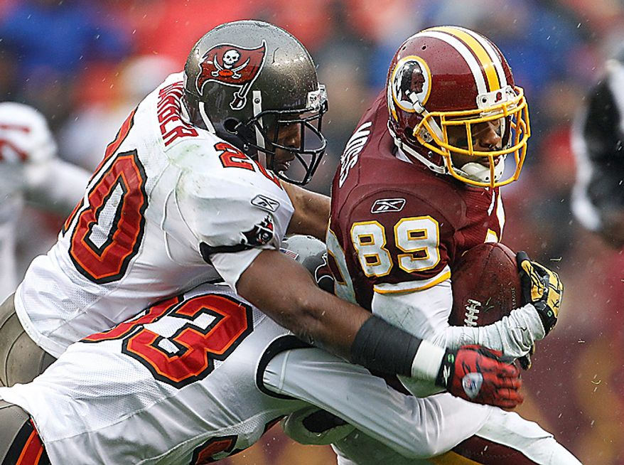 Tampa Bay Buccaneers cornerback Ronde Barber (20) and cornerback Elbert Mack (33) hang on to Washington Redskins wide receiver Santana Moss (89) during the first half of an NFL football game in Landover, Md., Sunday, Dec. 12, 2010. (AP Photo/Evan Vucci)