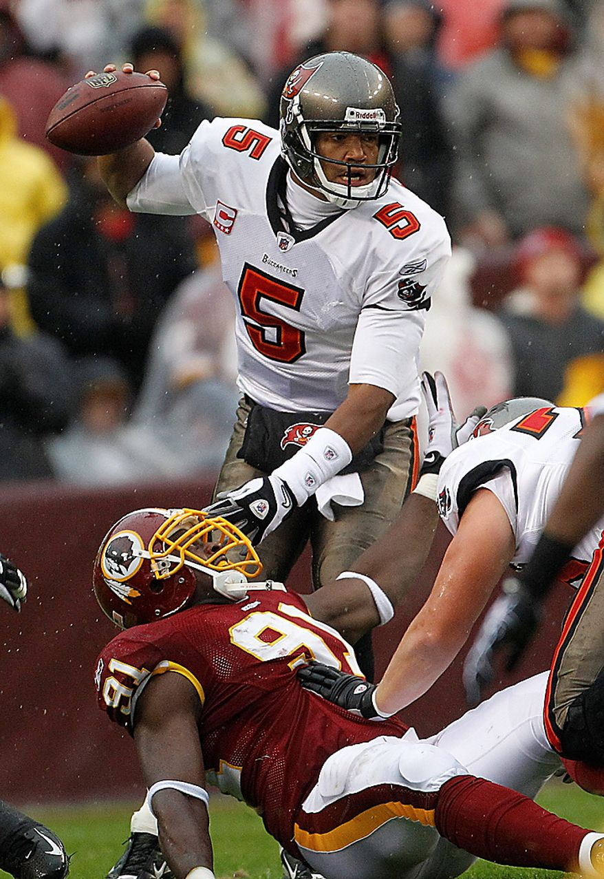 Tampa Bay Buccaneers quarterback Josh Freeman pushes Washington Redskins defensive end Vonnie Holliday (91) out of the way as he looks for an opening to throw during the first half of an NFL football game in Landover, Md., Sunday, Dec. 12, 2010. (AP Photo/Evan Vucci)