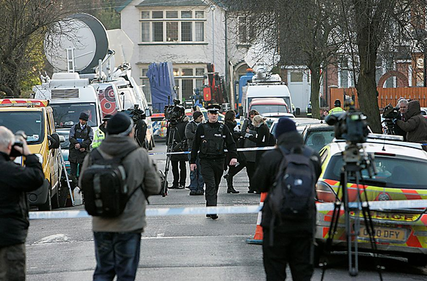 """The media gather as a police officer walks outside the house which was searched by British police in Luton, England, Monday, Dec. 13, 2010. A Swedish prosecutor says police are """"98 percent"""" certain the Stockholm suicide bomber is 28-year-old Taimour Abdulwahab who is a Swedish citizen but also lived several years in Britain. Prosecutor Tomas Lindstrand Monday said Abdulwahab has his roots in the Middle East and has been a Swedish citizen since 1992. Lindstrand said Abdulwahab was also the registered owner of the car that exploded in Stockholm shortly before the suicide blast Saturday. (AP Photo/Akira Suemori)"""