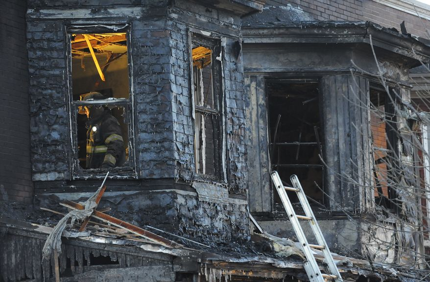 Firefighters investigate the scene of an early-morning, two-alarm fire in Baltimore on Tuesday. Three children were among the six people killed as flames engulfed their row house. (Baltimore Sun via Associated Press)