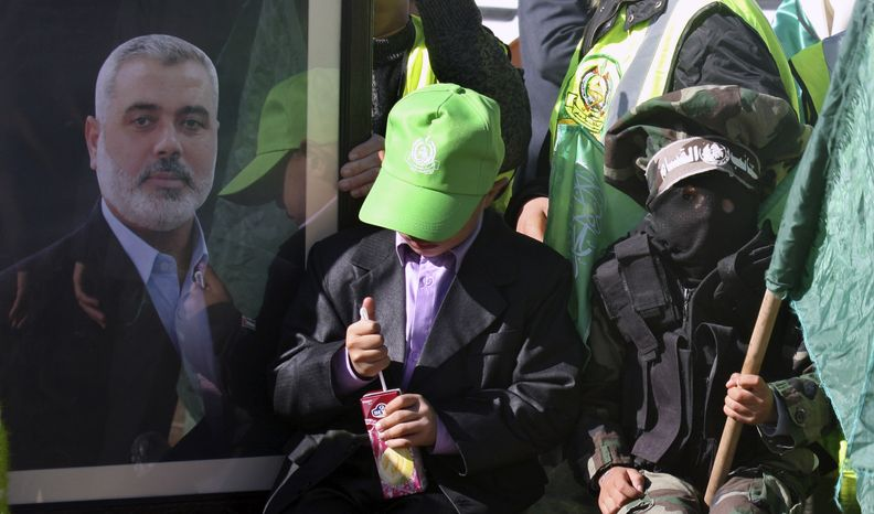 ** FILE ** Palestinian children, one masked and waving a green Islamic flag, sit near a photo of Gaza's Hamas prime minister, Ismail Haniyeh, during a rally to mark the 23rd anniversary of the group's founding, in Gaza City, Gaza Strip, on Tuesday, Dec. 14, 2010. (AP Photo/Majed Hamdan)