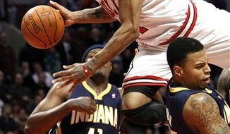 Chicago Bulls point guard Derrick Rose, center, falls to the ground as Indiana Pacers as forward James Posey and teammate Taj Gibson watches, during the second half of an NBA basketball game Monday, Dec. 13, 2010, in Chicago. The Bulls won 92-73. (AP Photo/Charles Rex Arbogast)