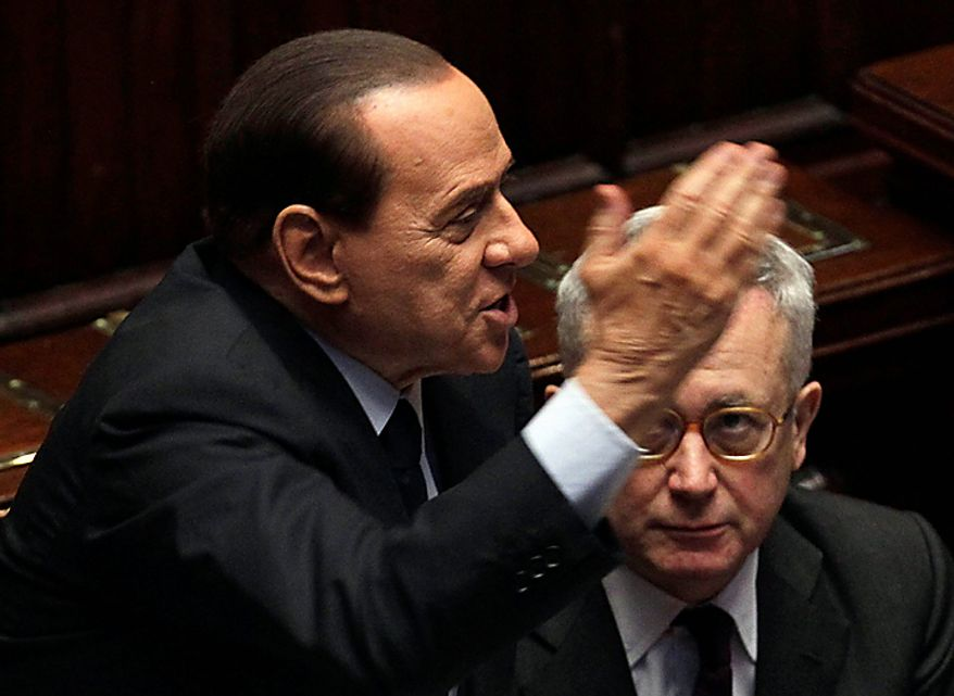Italian Premier Silvio Berlusconi gestures as Economic minister Giulio Tremonti sits beside him, at the Chamber of Deputies in Rome, Tuesday, Dec. 14, 2010. Premier Silvio Berlusconi has survived a confidence vote in the Italian Senate, but another, riskier vote follows in the lower house. Berlusconi had been expected to win the Senate vote on a motion in support of the government that had been brought by his allies. The vote Tuesday was 162-135. The showdown in parliament follows a dramatic fallout with his one-time closest ally, Gianfranco Fini. The breakup potentially deprives Berlusconi of a majority in the lower house, and that vote later Tuesday will hang on a few undecided lawmakers. (AP Photo/Gregorio Borgia)