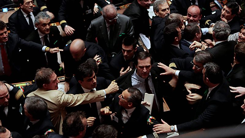 Lawmakers scuffle during a voting session at the Chamber of Deputies in Rome, Tuesday, Dec. 14, 2010. Premier Silvio Berlusconi has survived a confidence vote in the Italian Senate, but another, riskier vote follows in the lower house. Berlusconi had been expected to win the Senate vote on a motion in support of the government that had been brought by his allies. The vote Tuesday was 162-135. The showdown in parliament follows a dramatic fallout with his one-time closest ally, Gianfranco Fini. The breakup potentially deprives Berlusconi of a majority in the lower house, and that vote later Tuesday will hang on a few undecided lawmakers. (AP Photo/Gregorio Borgia)
