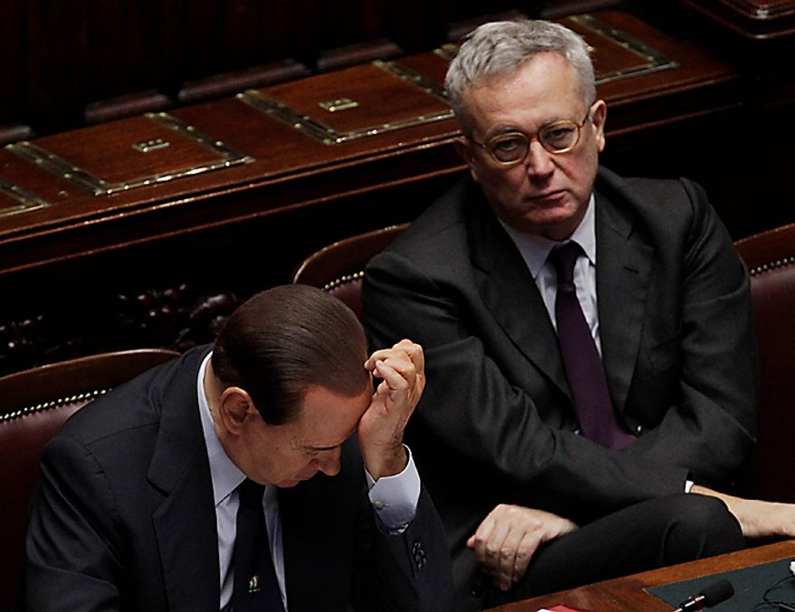 Italian Premier Silvio Berlusconi, left, reacts as he sits beside Economic minister Giulio Tremonti at the Chamber of Deputies in Rome, Tuesday, Dec. 14, 2010. Premier Silvio Berlusconi has survived a confidence vote in the Italian Senate, but another, riskier vote follows in the lower house. Berlusconi had been expected to win the Senate vote on a motion in support of the government that had been brought by his allies. The vote Tuesday was 162-135. The showdown in parliament follows a dramatic fallout with his one-time closest ally, Gianfranco Fini. The breakup potentially deprives Berlusconi of a majority in the lower house, and that vote later Tuesday will hang on a few undecided lawmakers. (AP Photo/Gregorio Borgia)
