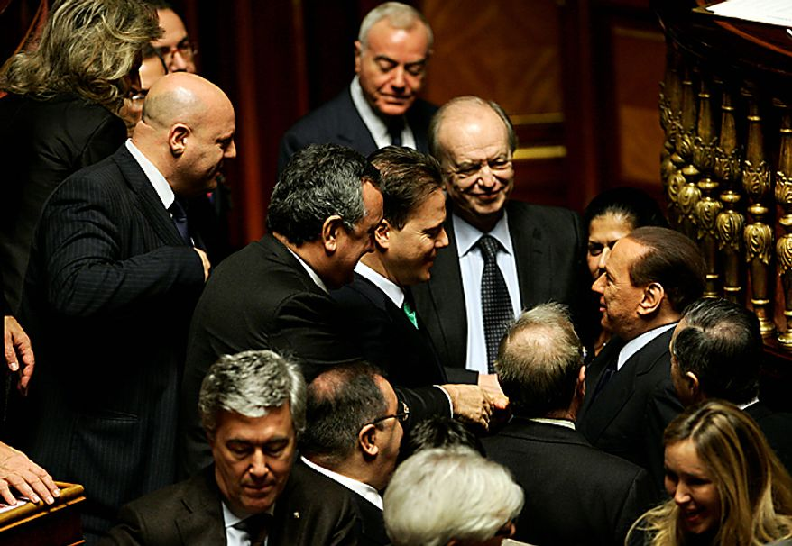 Italian Premier Silvio Berlusconi, right, talks to senators during a parliament debate, at the Senate in Rome, Tuesday, Dec. 14, 2010. Premier Silvio Berlusconi's political fate lies in the hands of a few swing lawmakers who will decide the outcome of confidence votes in the Italian parliament following a slew of scandals and political infighting. Parliament debate resumes Tuesday with a vote in the Senate scheduled to begin at 1030 GMT (5:30 a.m. EST), which the premier is expected to win. The risk lies in the lower Chamber of Deputies, where Berlusconi's split with longtime ally and Chamber speaker Gianfranco Fini has potentially deprived him of a majority. (AP Photo/Riccardo De Luca)